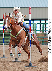 Young woman racing a horse in a pole bending competiton at a rodeo.