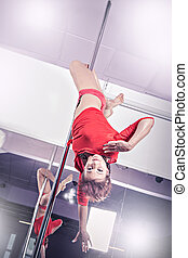 Pole dance - a women in sport dress pole dancing at the...