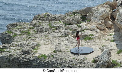 Pole dance fitness exercise on a rock at Cape Tarkhankut....