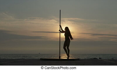 Pole dance fitness exercise on the beach at sunset.