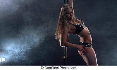 Pole dance. Girl dancing at camera temptingly