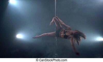 Pole dance in studio. View of professional dancer