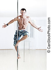 Young strong pole dance man.