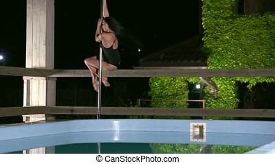 Pole dance performance at night beside swimming pool