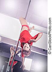 Pole dance - a women in sport dress pole dancing at the...