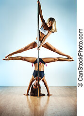 Pole dance women - Two young slim pole dance women.