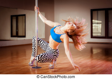 pole dance - young pretty girl pole dancing in a dance hall
