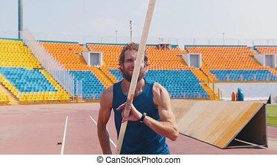 Pole vault - a bearded athletic man holding a pole and...