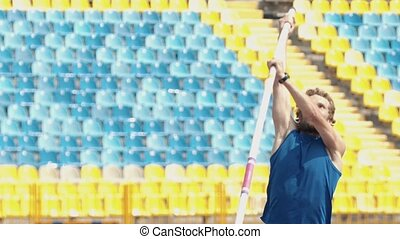 Pole vault - a bearded athletic man in blue shirt jumping...