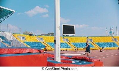 Pole vault - a bearded athletic man runs up holding a pole...