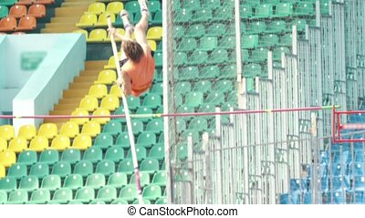 Pole vault - a man in orange shirt jumps over the bar. Mid...
