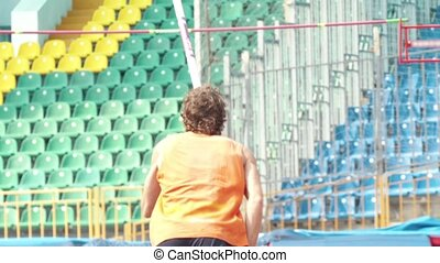 Pole vault - a man in orange shirt run up holding a pole in...