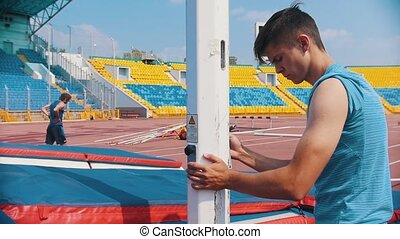 Pole vault - a man lowering the bar for the jumping. Mid...
