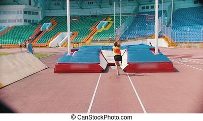 Pole vault - A young athletic woman jumps over the bar -...