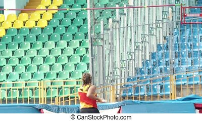 Pole vault - A young athletic woman with pigtails jumps over...