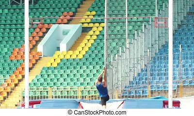 Pole vault - a young man in blue shirt jumps over the bar....
