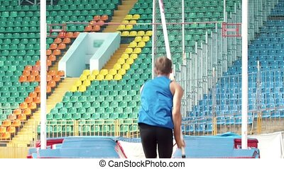 Pole vault - a young man prepares to runs up holding a pole....