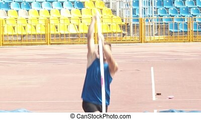 Pole vault - a young man running up and jumping over the bar...