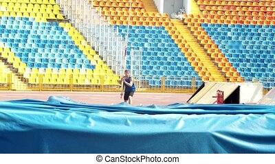Pole vault - a young man running up holding a pole - indoors