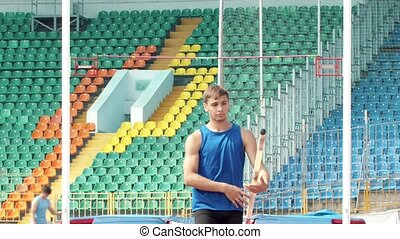 Pole vault - a young man walking to the start point holding...