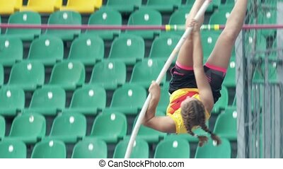 Pole vault - A young sportswoman jumps over the bar. Mid...