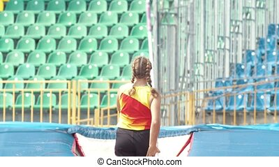 Pole vault - a young woman prepares to runs up before the...
