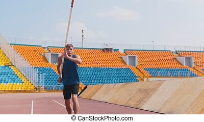 Pole vault - an athletic man breaths and starts running...