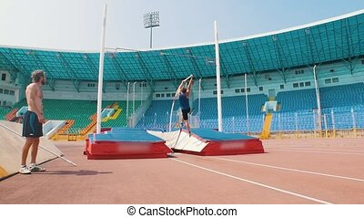 Pole vault - an athletic man jumping above the pole and...