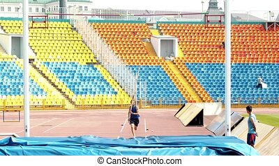 Pole vault - an athletic man running up and rest against the...