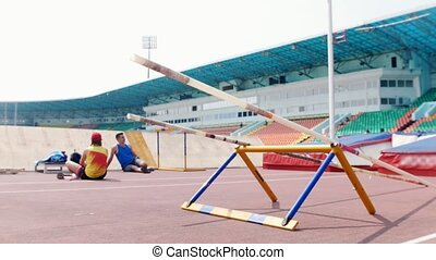 Pole vault - men sitting on the track and talking to each...