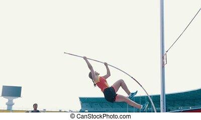 Pole vault training - a woman jumping over the bar - a man...