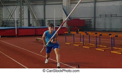 Pole vault training - a young man in blue shirt breathing in and out and starts running up before jumping. Mid shot
