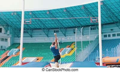 Pole vault training - an athletic man jumping over the bar...