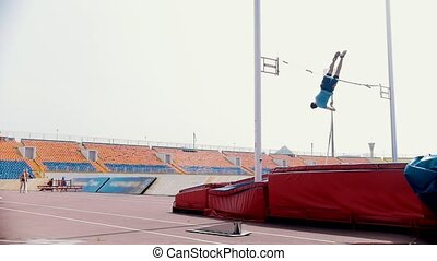 Pole vault training - an athletic man jumping over the bar....