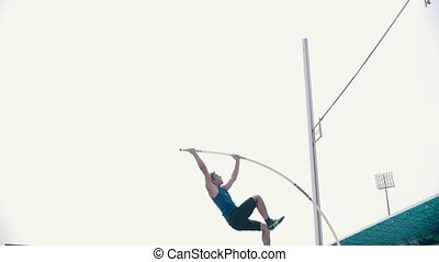Pole vault training - an athletic man perfectly jumping over...