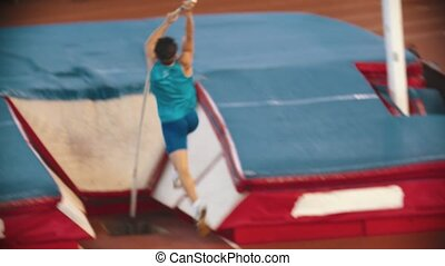 Pole vault training on the stadium - a young man running up and successfully jumps over the bar. Mid shot