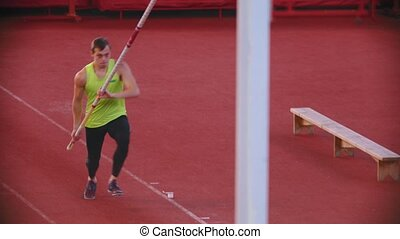 Pole vault training on the stadium - an athletic man performing his jump attempt. Mid shot