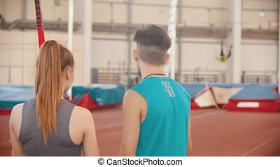 Pole vault - young man and woman standing on the stadium and looking at other sportsmen training. Mid shot