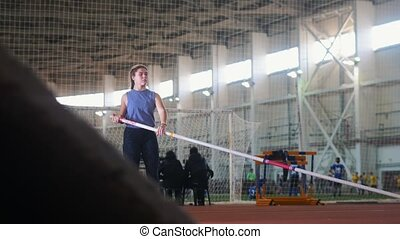 Pole vaulting in the indoors stadium - young woman with pigtails raises up the pole and starts running. Mid shot