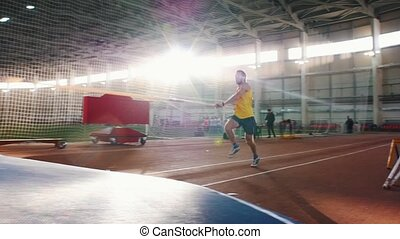 Pole vaulting indoors - a man in yellow shirt performing a jumping over the bar in the stadium. Mid shot