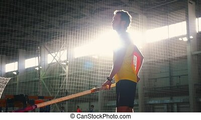 Pole vaulting indoors - a man in yellow shirt standing on the track with a pole and preparing for taking on on the jump. Mid shot