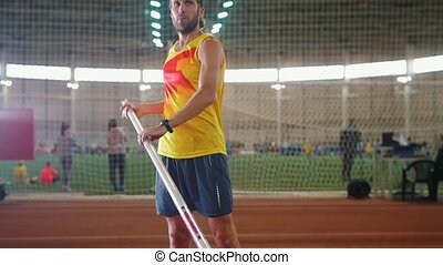 Pole vaulting indoors - a man in yellow shirt standing on the track with a pole and raising it up. Mid shot