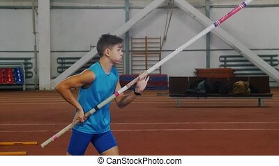 Pole vaulting indoors - a young man in blue shirt breathing in and out and starts running up before jumping. Mid shot