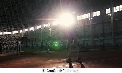 Pole vaulting indoors - a young woman prepares to the jumping - starts running up. Mid shot