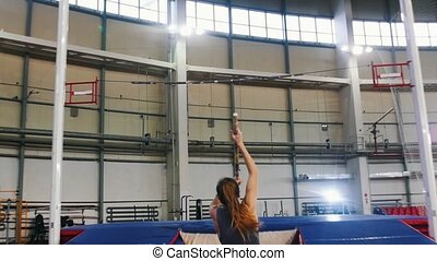 Pole vaulting indoors - a young woman with ponytail running up and jumping over the bar - touches the bar. Mid shot