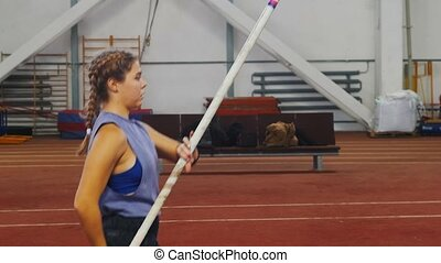 Pole vaulting indoors - young woman with pigtails preparing for the jump - running up - jumping over the bar. Mid shot