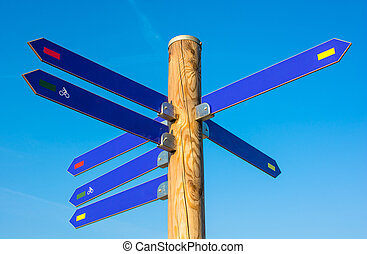 Pole with numerous direction arrows - Wooden pole with...