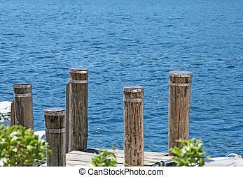 Poles of a pier stainding over a blue lake