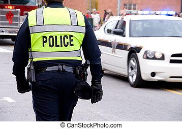 Police - AQ policeman walking by a patrol car on the street.