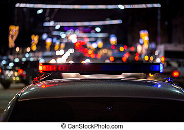 police car lights at night in city with selective focus and bokeh